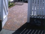 Red clay paver patio with white picket fence
