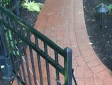 Red clay paver walkway and wrought-iron gate