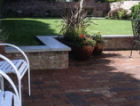 Red clay paver patio with brick wall