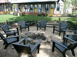 Outdoor seating around open firepit with scenic overview