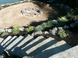 Stone stairway down to rock ringed firepit
