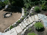 Stone steps descending through retaining wall to a rock ring firepit