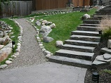 Lighted gravel walkway up with stone steps