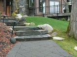Paver pathway with landscape lighting and stone steps