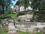 Multiple tiers of drystacked retaining walls and steps