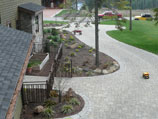 Paver walkway with flower beds and raised garden beds