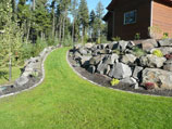 Boulder retaining wall with paver edging