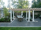 Flower beds in paver patio with custom pergola