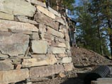 Curved retaining wall using naturally stacked stone quarried in Clark Fork