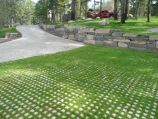 Paver driveway with grass grid pavers and boulder wall constructed of ledge stone supplied by Stutzke Stone of Clark Fork