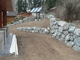 Natural rock retaining wall split into two tiers