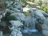 Meandering water feature of natural boulders adding ambiance