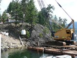 Offloading landscape construction material from a barge via crane